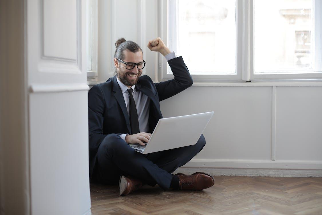 Man In Black Suit Sitting On The Floor