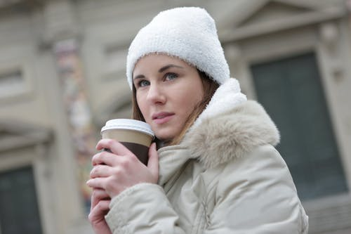 Woman in White Jacket Holding White Disposable Cup