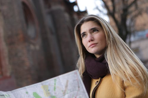 Woman in Purple Knit Scarf and Brown Coat Holding a City Map