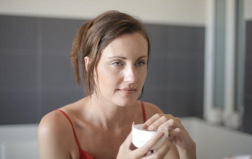 Woman in Red Tank Top Holding White Ceramic Mug