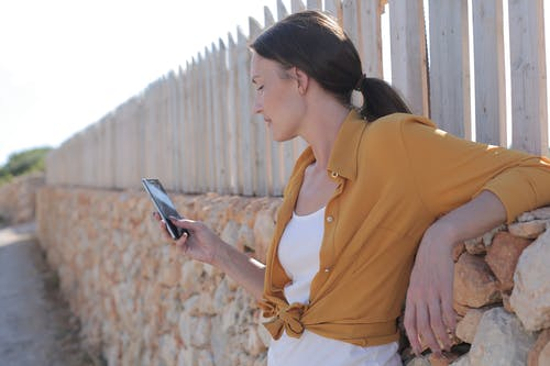 Woman In Yellow Long Sleeve Holding A Smartphone