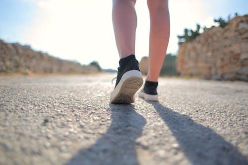 Person in Black Socks and Black Sneakers Walking on Gray Asphalt Road