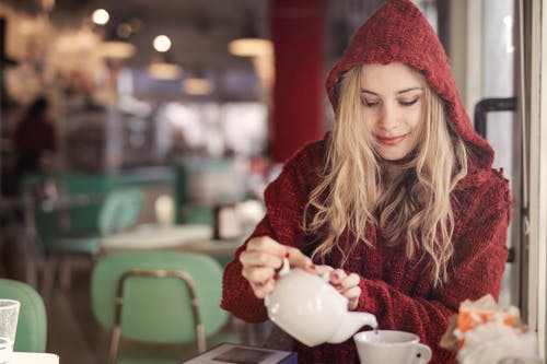 Woman in Red Sweater Holding White Ceramic Teacup