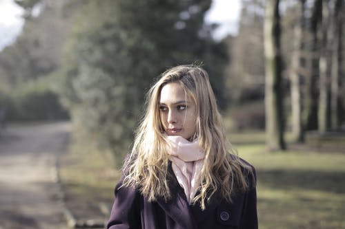Woman in Violet Coat with Pink Scarf Standing Near Green Trees