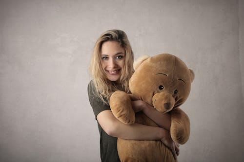Woman in Gray Shirt Hugging Brown Bear Plush Toy