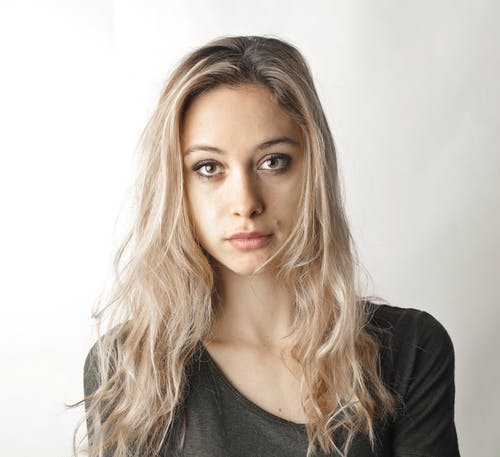 Woman in Gray Shirt Standing Beside White Wall