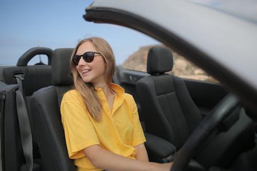 黃色襯衫,戴著黑色太陽鏡,坐在車上的女人
