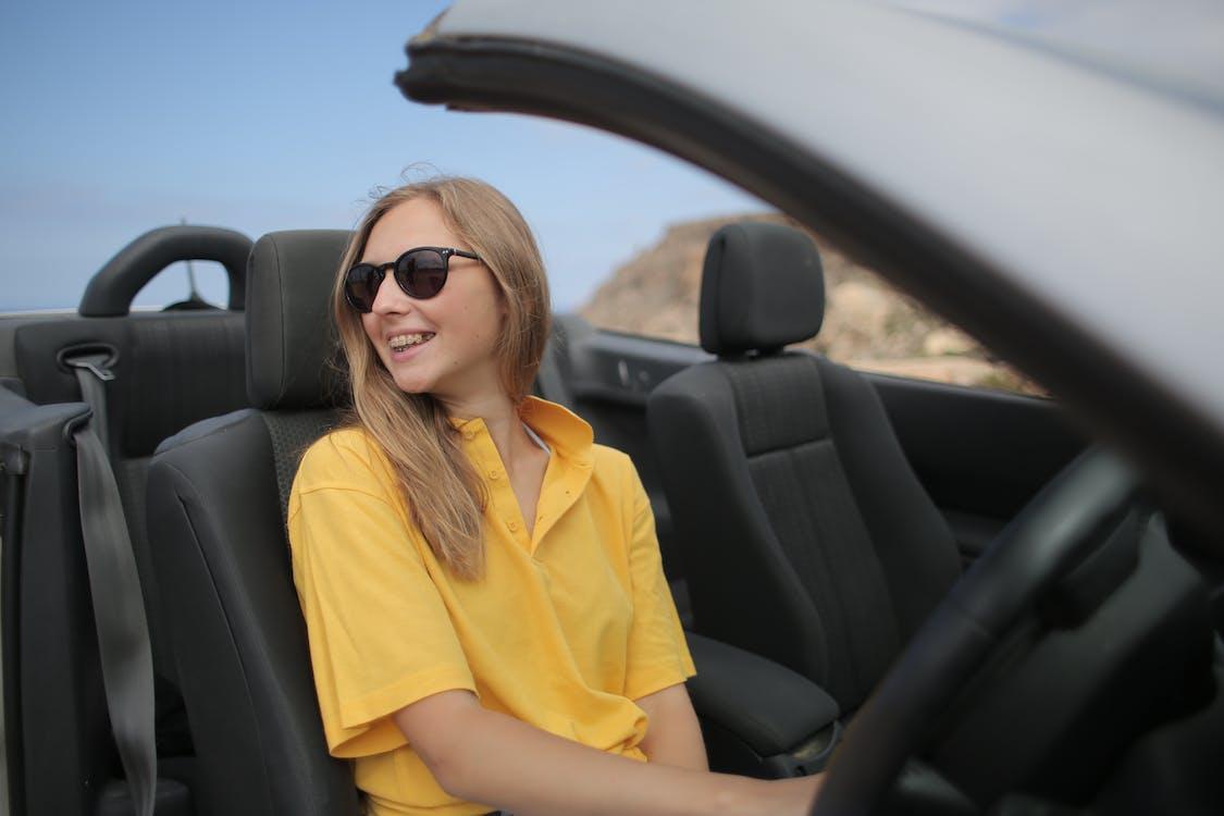 Woman In Yellow Shirt Wearing Black Sunglasses Sitting On Car