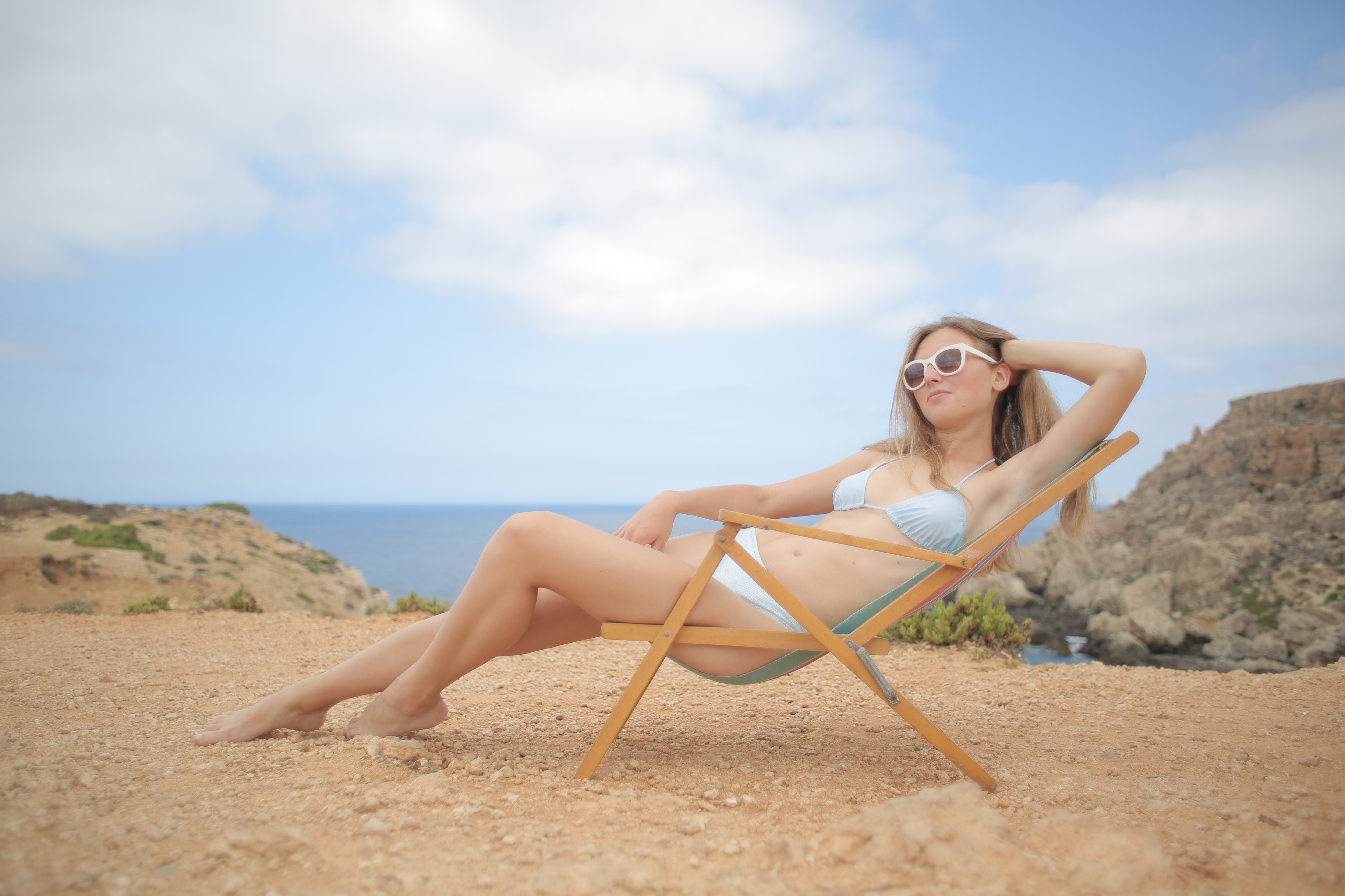 Woman In Blue Swimsuit Sitting On Wooden Beach Chair Free Stock Photo