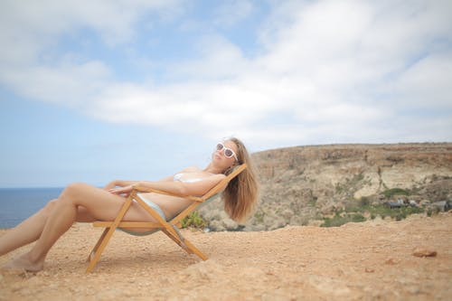 Woman In White Bikini Sitting On Folding Chair