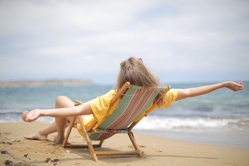 Photo of Woman Reclining on Wooden Folding Chair