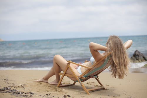 Woman in Blue Bikini Sitting on Brown Wooden Folding Chair on Beach