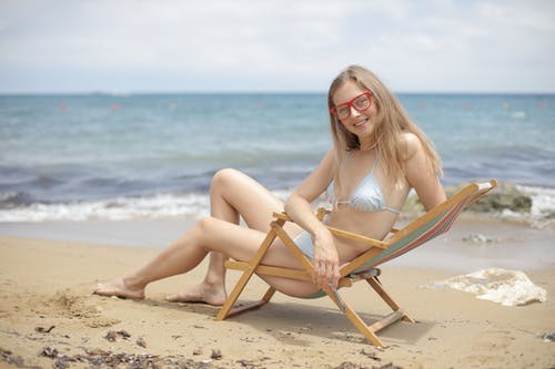 Woman in Bikini Sitting on Brown Wooden Folding Chair on Beach