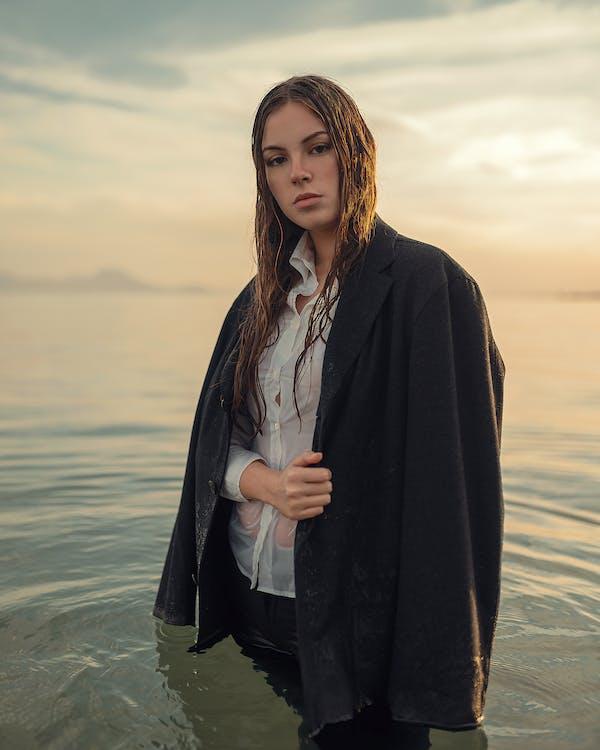 Woman in Black Coat Standing on Beach