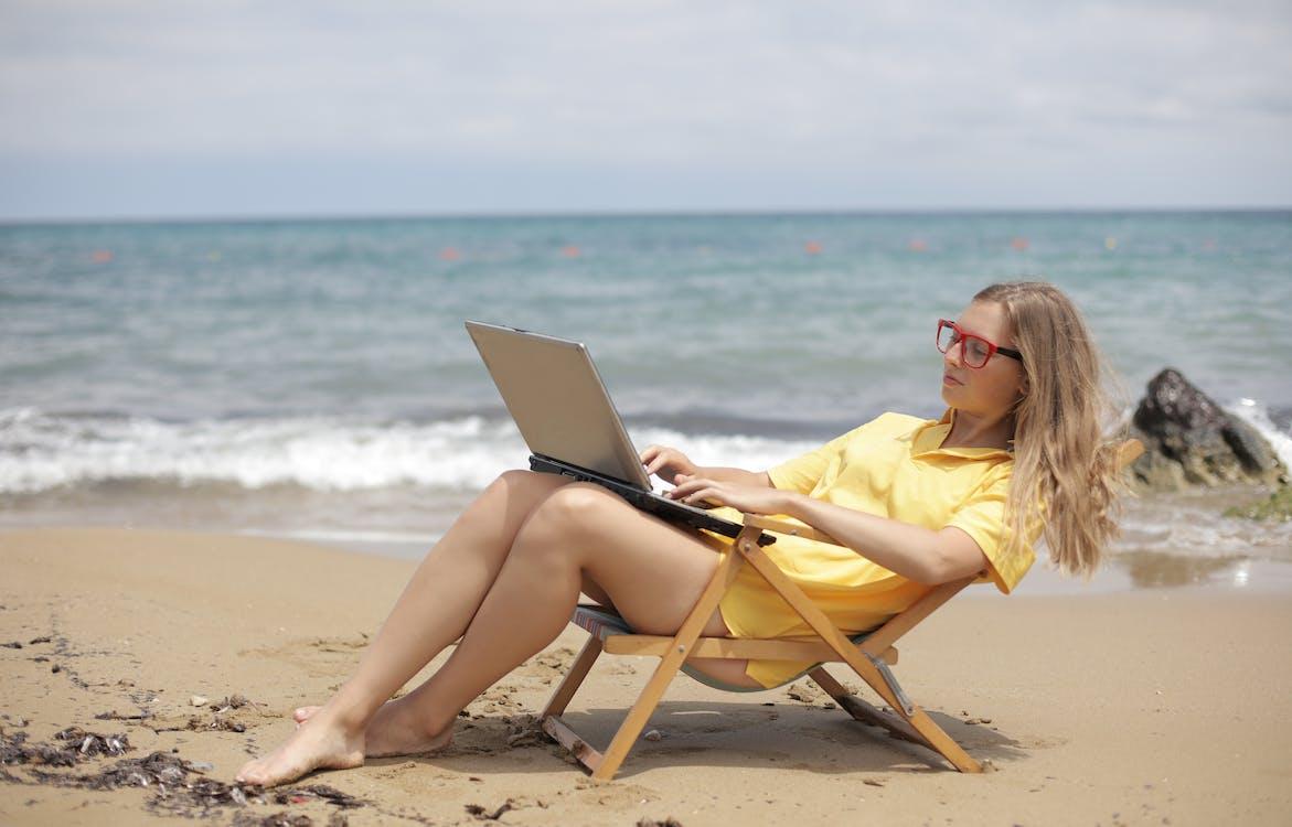 Mujer En Camisa Amarilla Sentada En Una Silla Plegable De Madera Marrón En La Playa