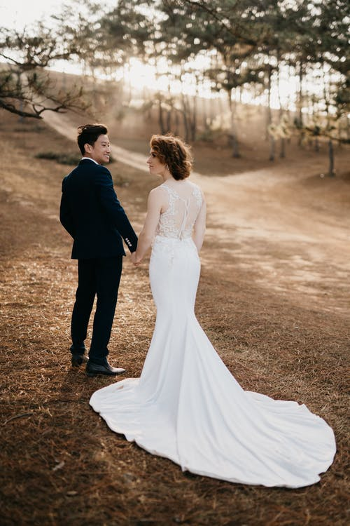 Woman in White Wedding Gown Holding Hands with Man in Black Suit
