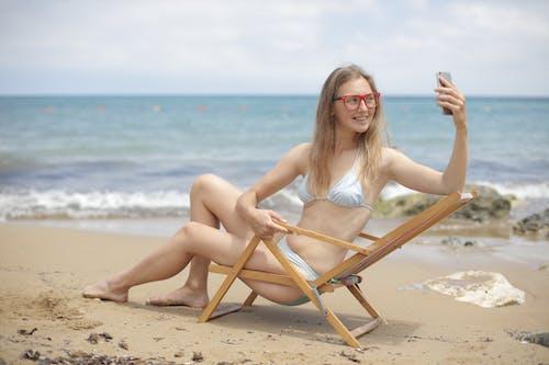 Woman in Bikini Sitting on Wooden Folding Chair on Beach