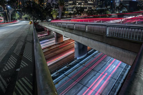 Timelapse Photography of Vehicles Traveling Bridge and Road at Night