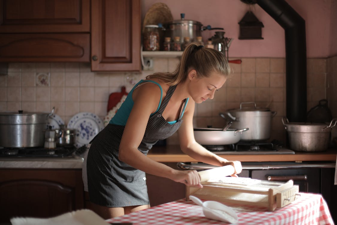 Woman in Blue Tank Top Using a Rolling Pin