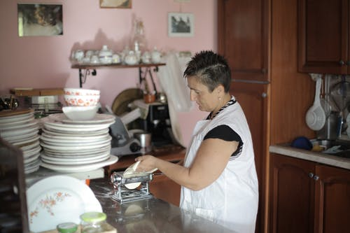 Woman in White Dress Making a Tortillas