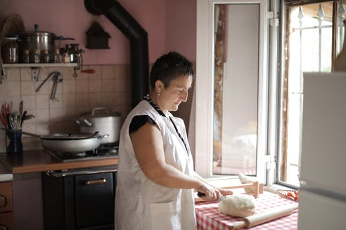 Woman in White Apron Standing in Kitchen