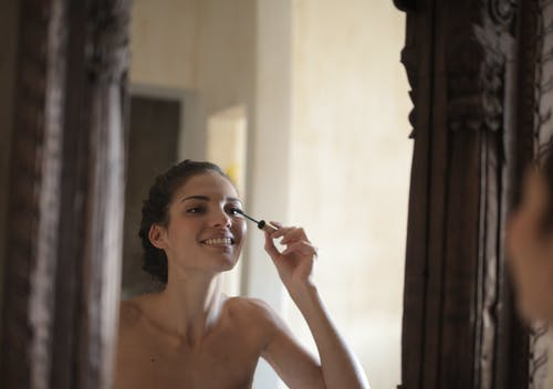Photo of Woman Smiling While Applying Mascara