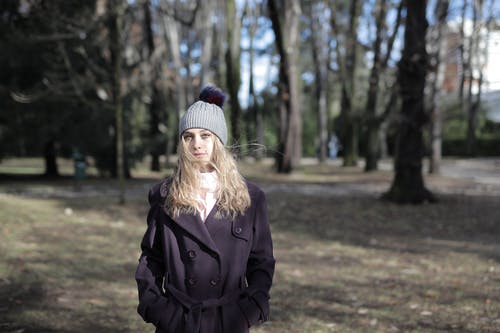 Shallow Focus Photo of Woman Wearing Bonnet and Violet Coat