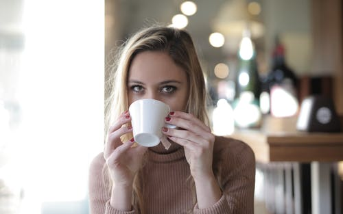 Woman in Sweater Holding White Ceramic Mug