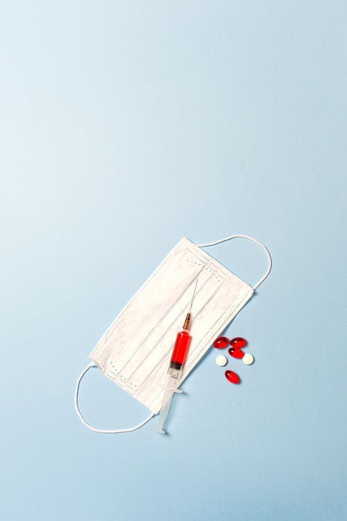 Syringe and Pills on Blue Background