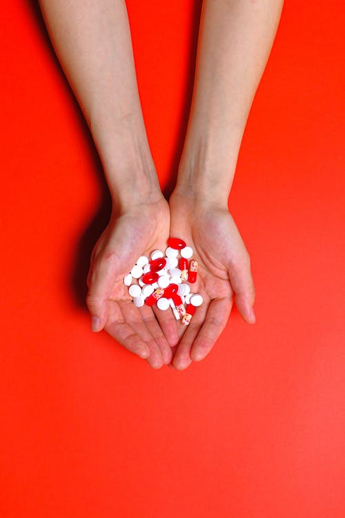 Person Holding White and Red Medical Pills and Capsules