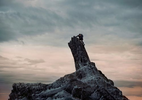 Man in Black Jacket Climbing on Rock Formation Under Cloudy Sky