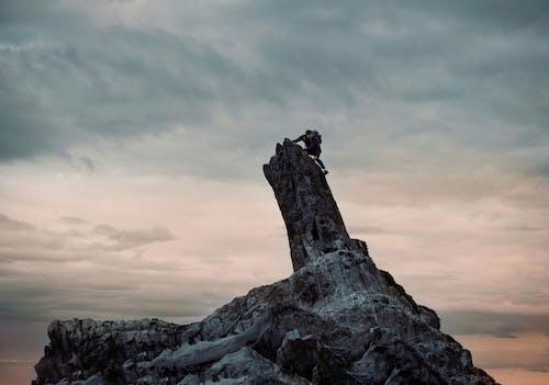 Man In Zwarte Jas Klimmen Op Rotsformatie Onder Bewolkte Hemel