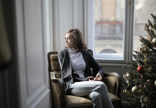 Woman in Black Jacket Sitting on Brown Armchair