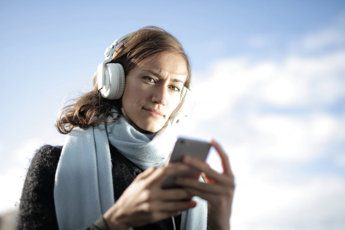 Woman Wearing Scarf While Holding Smartphone