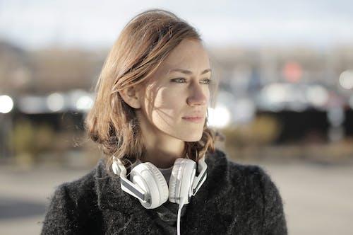 Mujer En Abrigo De Piel Negro Con Auriculares Blancos