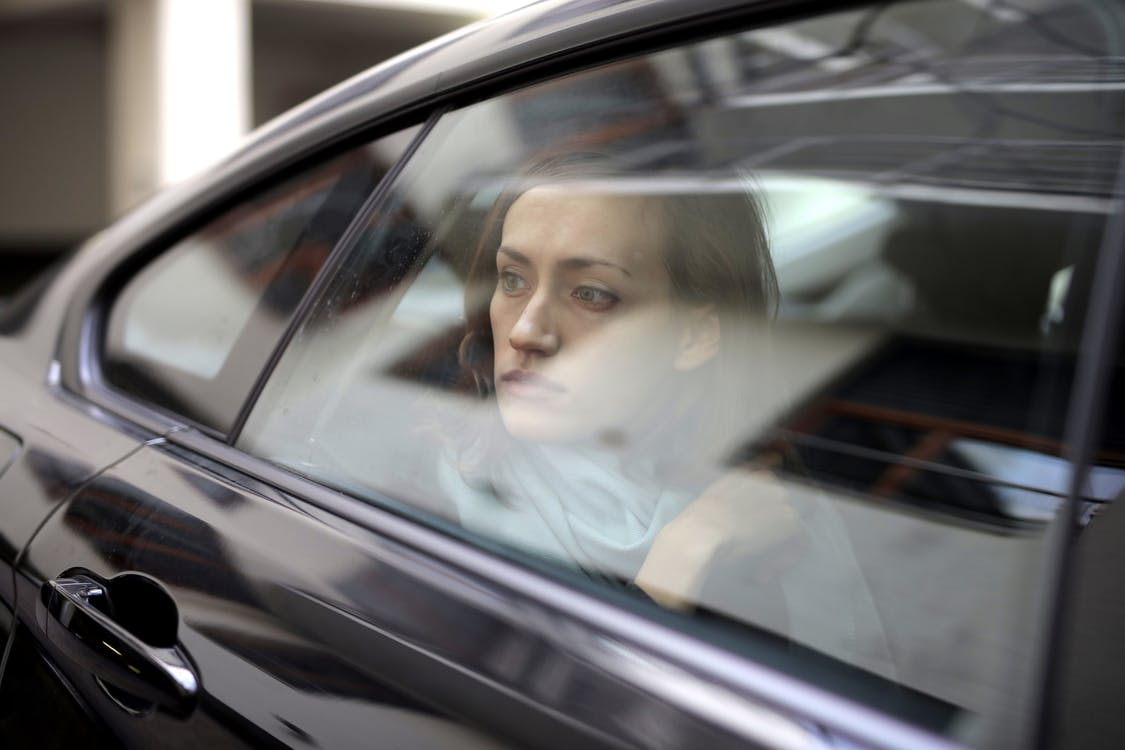 Woman Looking Out While Sitting Inside the Car