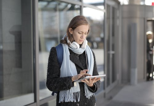 Woman in Black Fur Coat While Holding White Tablet