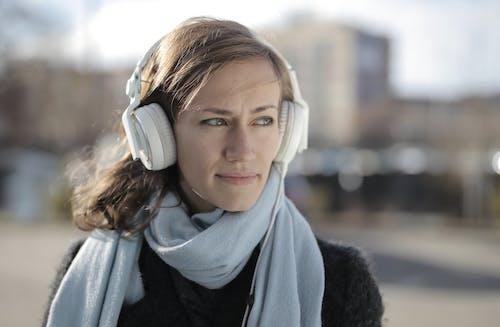Безкоштовне стокове фото на тему «білі навушники, використання, вираз обличчя»