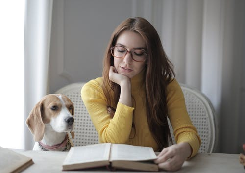 Woman in Yellow Sweater While Reading a Book