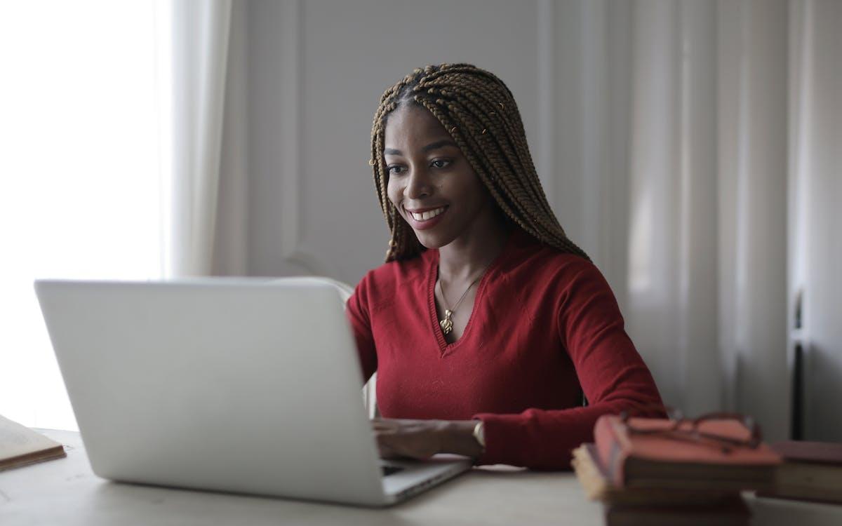 Woman in Red Long Sleeve Shirt Using Macbook