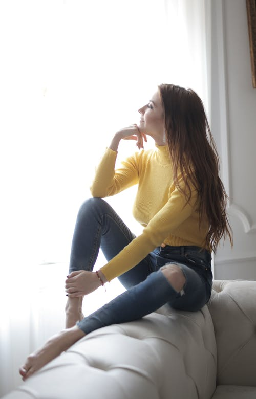 Woman in Yellow Long Sleeve Shirt and Blue Denim Jeans Sitting on Couch