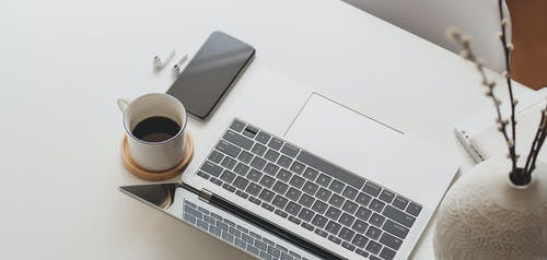 Silver Apple Keyboard Beside White Ceramic Mug on White Table