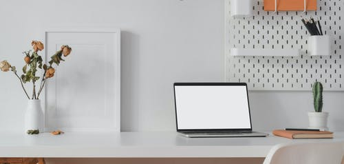 White Laptop Computer on White Wooden Table