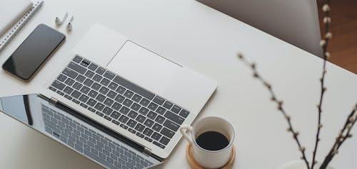 White and Black Laptop Computer Beside White Ceramic Mug