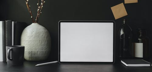 Tablet with notepads and decorations on table