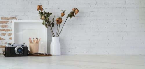 Simple design with dry flowers and photo camera