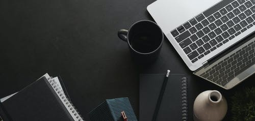 Elegant dark desk with laptop and notepads