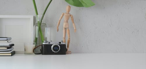 Retro photo camera with manikin on desk