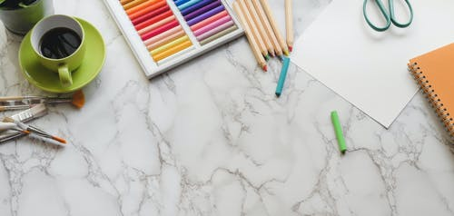 Colorful crayons and coffee cup on desk