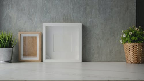 Photo of Empty Picture Frames Near Gray Wall